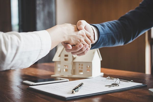 commercial realtor shaking hands with multi family real estate investor